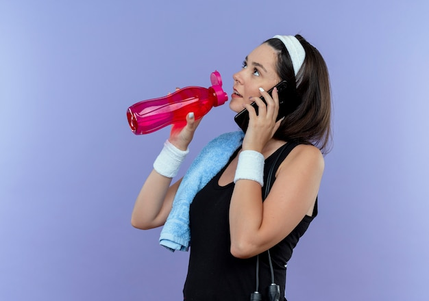 Młoda kobieta fitness w opasce z ręcznikiem na jej ramieniu wody pitnej podczas rozmowy na telefon komórkowy stojący na niebieskim tle