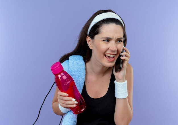 Młoda kobieta fitness w opasce z ręcznikiem na ramieniu trzymająca butelkę wody rozmawiająca przez telefon komórkowy z zirytowaną miną stojącą na niebieskim tle