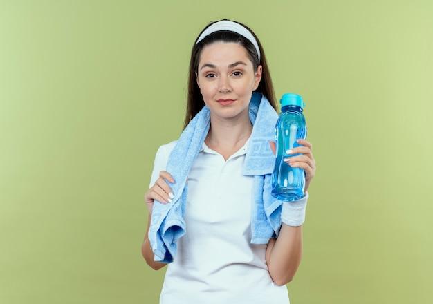 Młoda kobieta fitness w opasce z ręcznikiem na szyi, trzymając butelkę wody, patrząc na kamery, uśmiechając się pewnie stojąc na jasnym tle