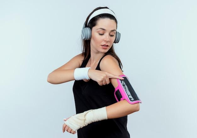 Młoda kobieta fitness w opasce ze słuchawkami, dotykając jej opaskę smartfona, patrząc pewnie stojąc na białej ścianie