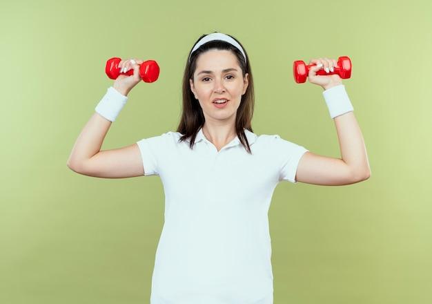 Młoda kobieta fitness w pałąku na głowę z hantlami patrząc pewnie stojąc na jasnym tle