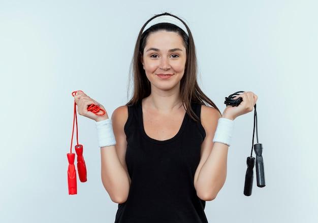 Młoda kobieta fitness w pałąku trzyma skakanki patrząc na kamery uśmiechnięty stojący na białym tle
