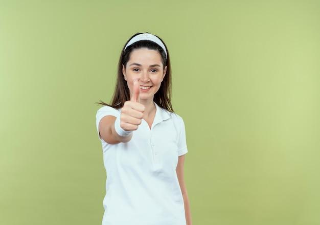 Młoda kobieta fitness w pałąku uśmiecha się radośnie pokazując kciuki do góry patrząc na aparat stojący na jasnym tle