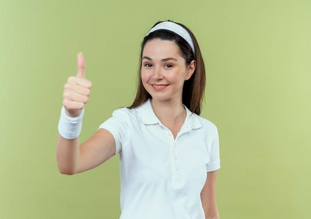 Młoda kobieta fitness w pałąku uśmiecha się radośnie pokazując kciuki do góry stojąc nad ścianą światła
