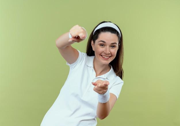 Młoda kobieta fitness w pałąku uśmiecha się radośnie z szczęśliwą twarzą, wskazując palcami wskazującymi na aparat stojący na jasnym tle