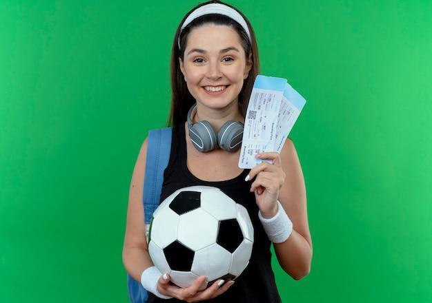 Młoda kobieta fitness w pałąku ze słuchawkami i plecakiem trzymając piłkę nożną i bilety lotnicze patrząc na kamery uśmiechnięty z radosną twarzą stojącą na zielonym tle