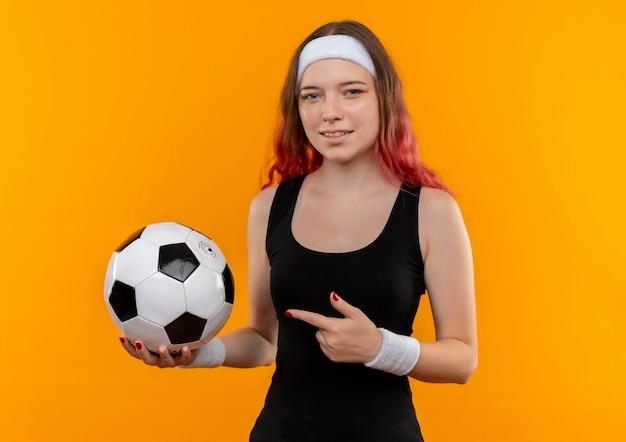 Młoda kobieta fitness w sportowej trzymając piłkę nożną wskazując palcem wskazującym na to uśmiechnięty stojący nad pomarańczową ścianą