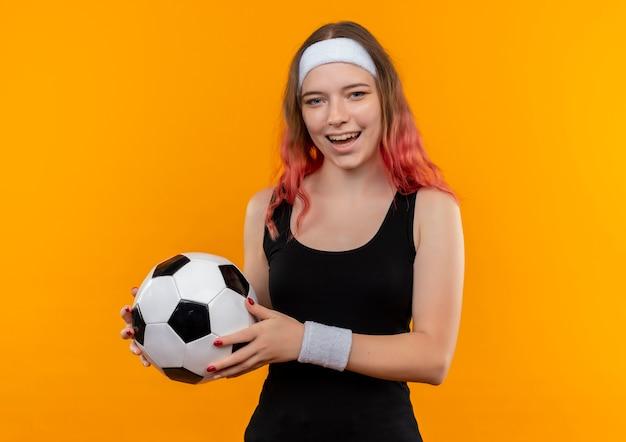 Młoda kobieta fitness w sportowej trzymając piłkę nożną z radosną buźką uśmiechnięty wesoło stojąc nad pomarańczową ścianą