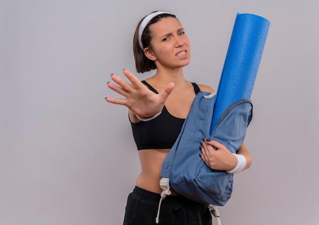 Młoda kobieta fitness w sportowej trzymając plecak z matą do jogi robi znak stopu z otwartą ręką z obrzydzonym wyrazem stojącym nad białą ścianą