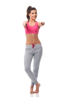Młoda kobieta fitness, wskazując na boku aparatu