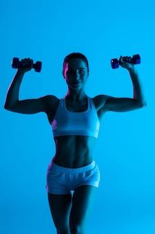 Młoda kobieta fitness z hantlami na białym tle na niebieskim tle światła