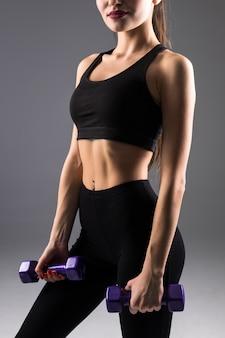 Młoda kobieta fitness z hantlami na szarej ścianie. sportowy styl życia.