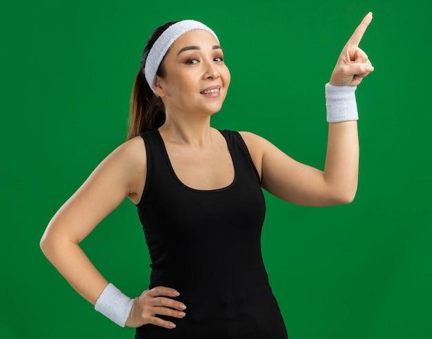 Młoda kobieta fitness z opaską i opaskami uśmiecha się pewnie wskazując palcem wskazującym w bok, stojąc nad zieloną ścianą