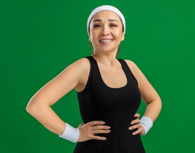 Młoda kobieta fitness z opaską i opaskami uśmiecha się pewnie z rękami na biodrze, stojąc nad zieloną ścianą