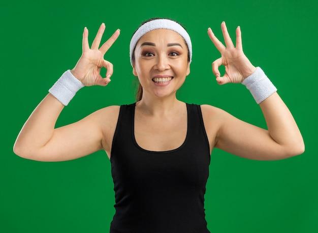 Młoda kobieta fitness z opaską i opaskami uśmiecha się radośnie pokazując znak ok stojący nad zieloną ścianą
