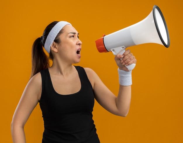Młoda kobieta fitness z opaską na głowę i opaskami krzyczącą do megafonu z agresywną ekspresją