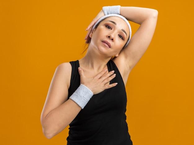 Młoda kobieta fitness z opaską na głowę i opaskami odczuwa dyskomfort dotykając jej głowy i klatki piersiowej, stojąc nad pomarańczową ścianą