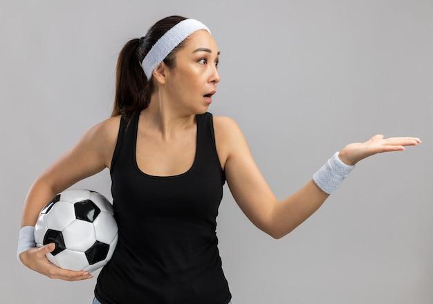 Młoda kobieta fitness z opaską na głowę i opaskami, trzymając piłkę nożną, patrząc na bok, myląc się z ramieniem stojącym nad białą ścianą