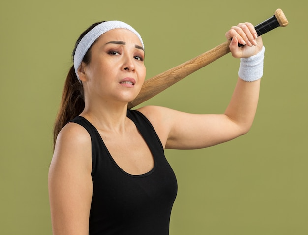 Młoda kobieta fitness z opaską na głowę i opaskami, trzymająca kij bejsbolowy z pewną miną