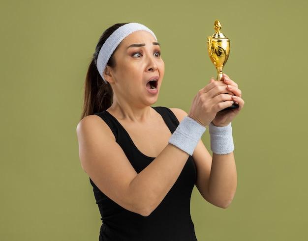 Młoda kobieta fitness z opaską na głowę i opaskami, trzymająca trofeum, patrząca na niego z rozczarowanym wyrazem twarzy stojącym nad zieloną ścianą