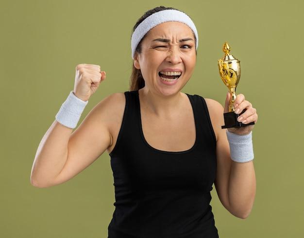 Młoda kobieta fitness z opaską na głowę i opaskami trzymająca trofeum zła i sfrustrowana zaciskająca pięść