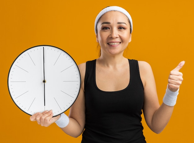 Młoda kobieta fitness z opaską na głowę i opaskami, trzymająca zegar ścienny, uśmiecha się radośnie pokazując kciuk w górę