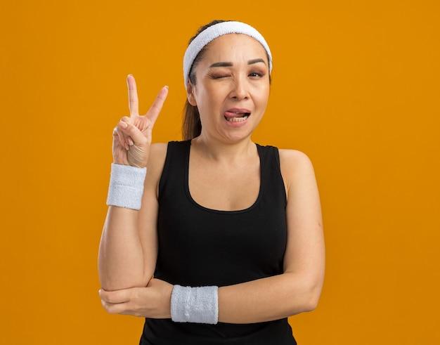 Młoda kobieta fitness z opaską na głowę i opaskami uśmiecha się i mruga pokazując znak v stojący nad pomarańczową ścianą