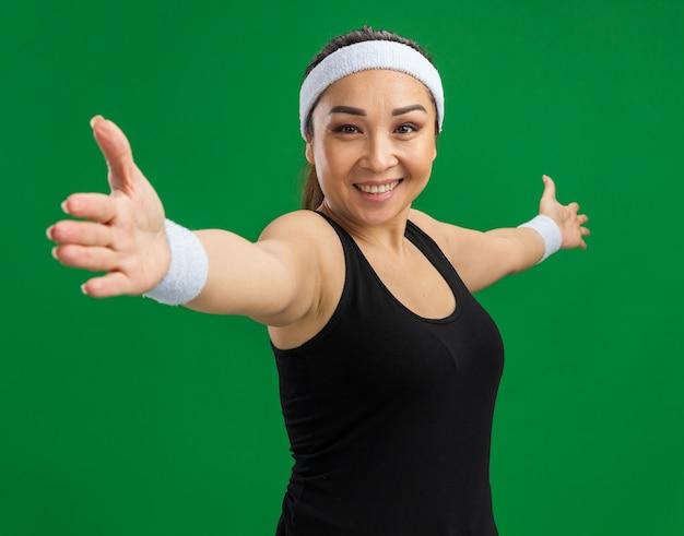 Młoda kobieta fitness z opaską na głowę i opaskami uśmiecha się pewnie wykonując ćwiczenia stojąc nad zieloną ścianą