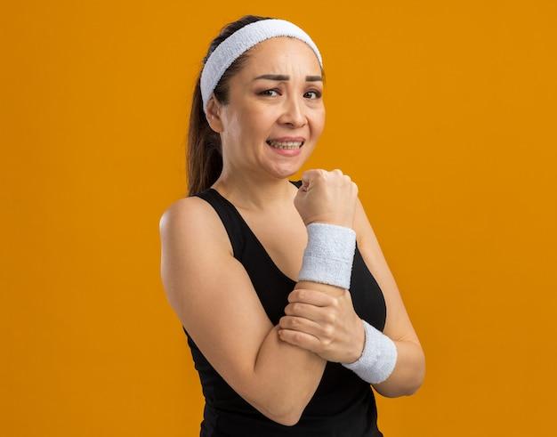 Młoda kobieta fitness z opaską na głowę i opaskami wygląda źle, dotykając jej ramienia, czując ból stojący nad pomarańczową ścianą