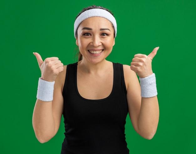 Młoda kobieta fitness z opaską na głowę i opaskami z uśmiechem na twarzy pokazując kciuk do góry stojący nad zieloną ścianą