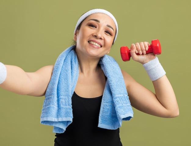 Młoda kobieta fitness z opaską na głowę i ręcznikiem na szyi, trzymająca hantle, wykonująca ćwiczenia, uśmiechnięta radośnie