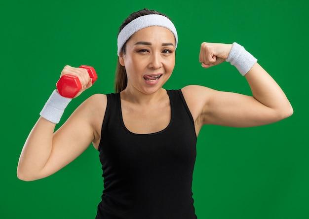 Młoda kobieta fitness z opaską na głowę z hantlami robi ćwiczenia podnoszące pięść pokazujące bicepsy uśmiechający się pewnie stojąc nad zieloną ścianą