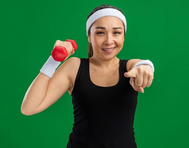 Młoda kobieta fitness z opaską na głowę z hantlami robi ćwiczenia uśmiechając się pewnie wskazując palcem wskazującym stojącym nad zieloną ścianą