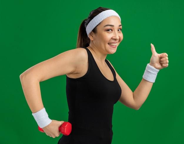 Młoda kobieta fitness z opaską na głowę z hantlami robi ćwiczenia uśmiechając się pokazując kciuk do góry stojący nad zieloną ścianą