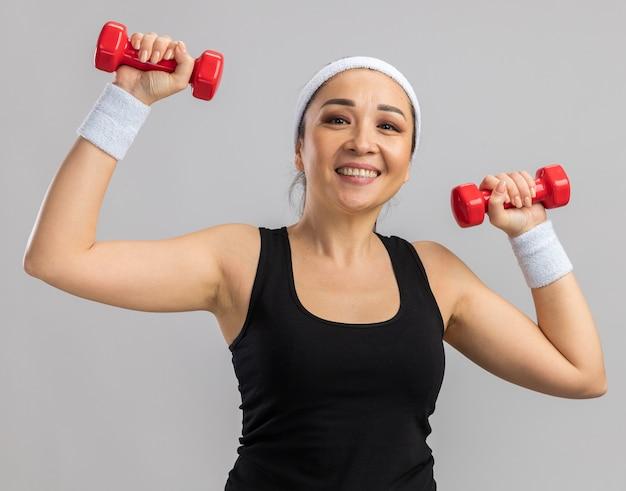 Młoda kobieta fitness z opaską na głowę z hantlami robi ćwiczenia, wygląda na zmęczoną i pewnie uśmiechniętą, stojąc nad białą ścianą