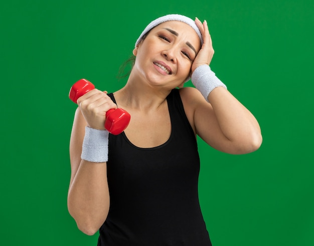 Młoda kobieta fitness z opaską na głowę z hantlami robi ćwiczenia, wygląda na zmęczoną i przepracowaną, stojąc nad zieloną ścianą