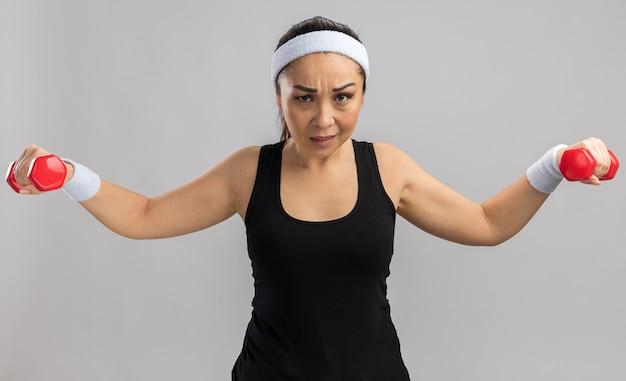 Młoda kobieta fitness z opaską na głowę z hantlami robi ćwiczenia, wyglądając na zmęczoną i pewną siebie, stojąc nad białą ścianą