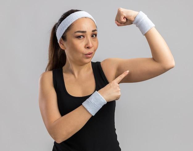 Młoda kobieta fitness z opaską na głowie i opaskami podnoszącymi pięść pokazującą siłę i moc stojącą nad białą ścianą