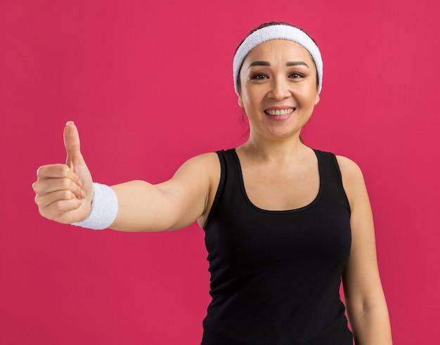 Młoda kobieta fitness z opaską uśmiecha się radośnie pokazując kciuk do góry stojący nad różową ścianą