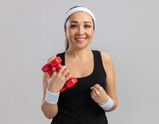 Młoda kobieta fitness z pałąkiem na głowę trzymająca hantle, wykonująca ćwiczenia zaciskając pięść, szczęśliwa i podekscytowana stojąc nad białą ścianą