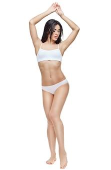 Młoda kobieta fitness z pięknym ciałem na białym tle