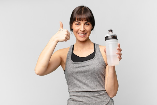 Młoda kobieta fitness z puszką na wodę