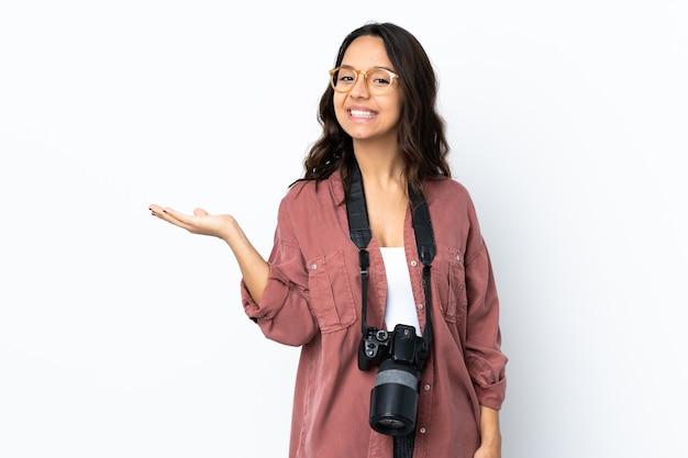 Młoda kobieta fotograf na pojedyncze białe ściany gospodarstwa copyspace wyimaginowane na dłoni, aby wstawić reklamę