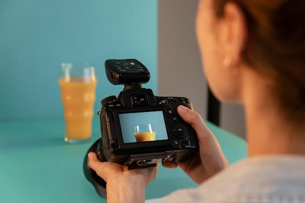 Młoda kobieta fotograf produktu w studio