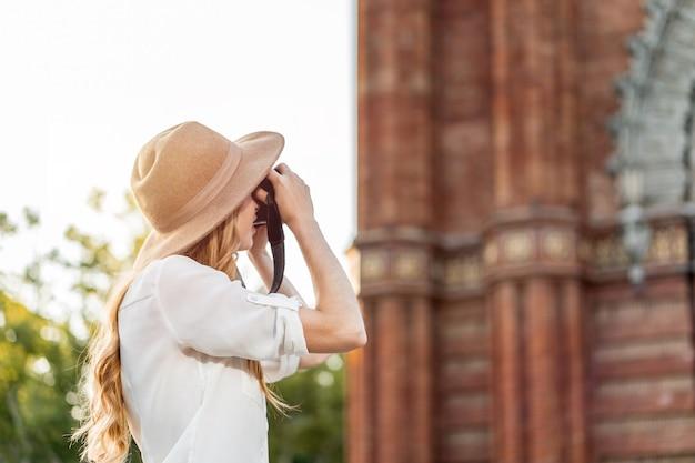 Młoda kobieta fotograf robi zdjęcia zabytków barcelony.