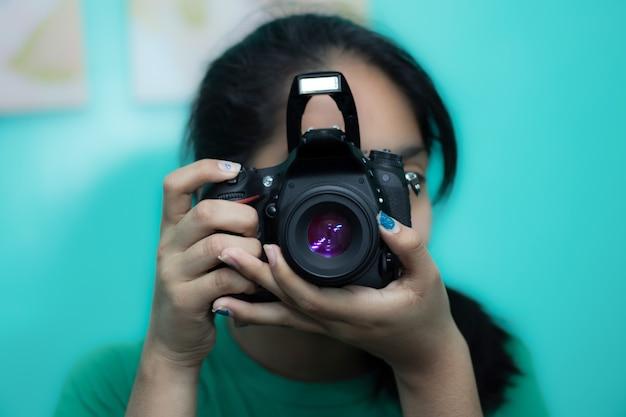 Młoda kobieta fotograf robi zdjęcie aparatem dslr