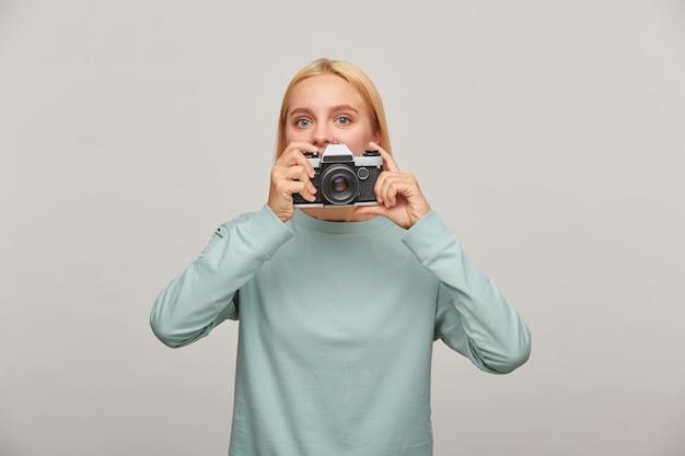 Młoda kobieta fotograf wychodzi zza obiektywu, trzymając aparat fotograficzny retro vintage