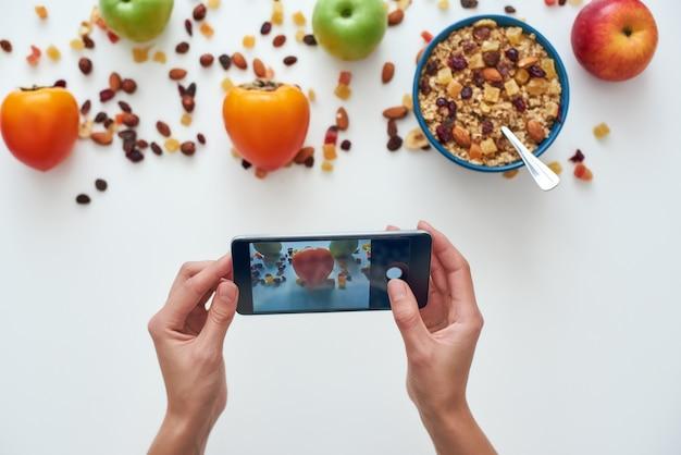 Młoda kobieta fotografuje jej śniadanie. dziewczyna je płatki śniadaniowe z orzechami, pestkami dyni, owsem i w misce z owocami. dziewczyna trzyma inteligentny telefon. zdrowa przekąska lub śniadanie rano.