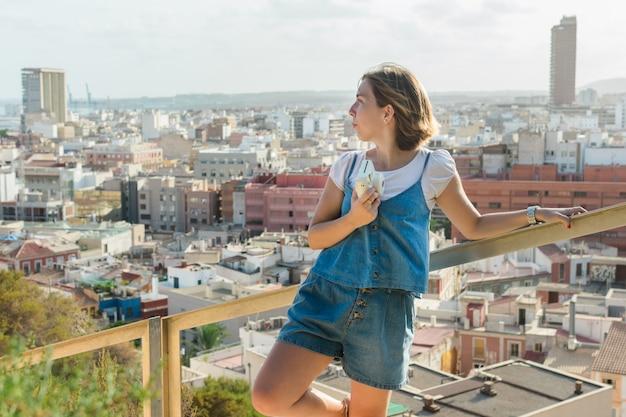 Młoda kobieta fotografuje natychmiastowym aparatem w mieście alicante