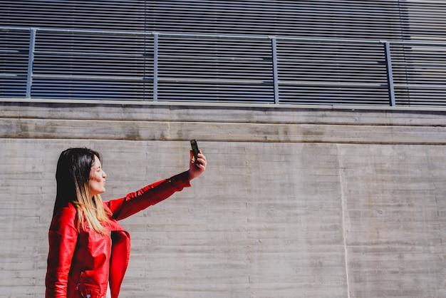 Młoda kobieta fotografuje się telefonem, aby wysłać selfie do swoich sieci społecznościowych.